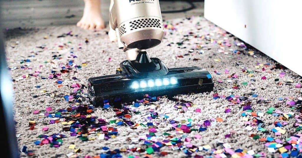 an image of the best rated stick vacuum being used to clean confetti from rug