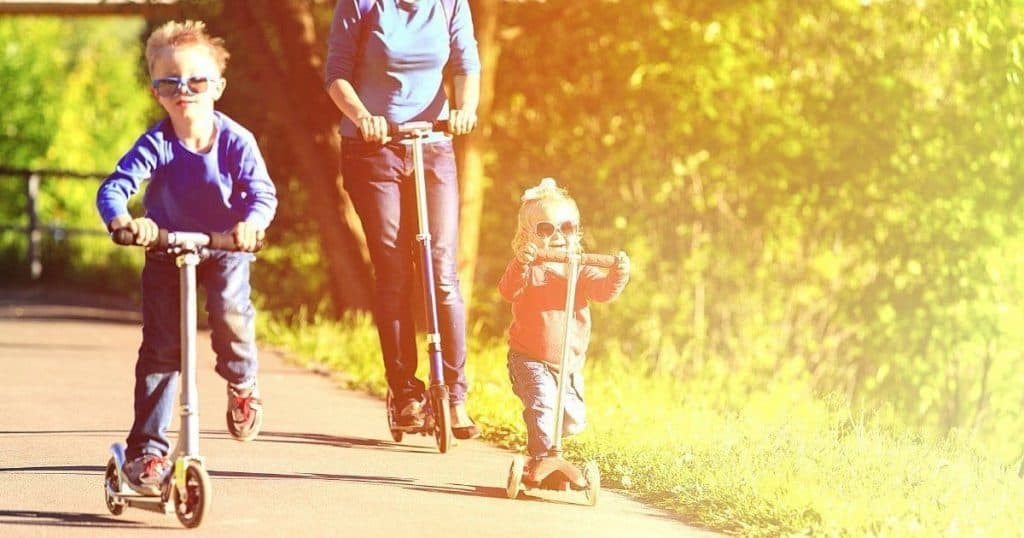 an image of a family with a boy and a toddler using the best child scooter