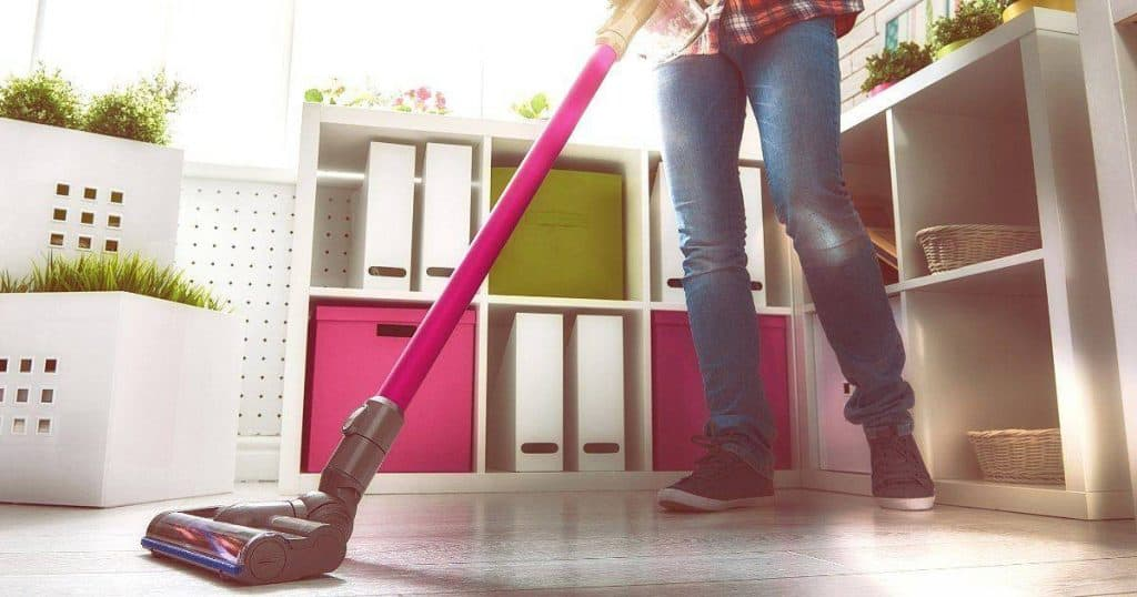 an image of a woman cleaning with the best lightweight stick vacuum