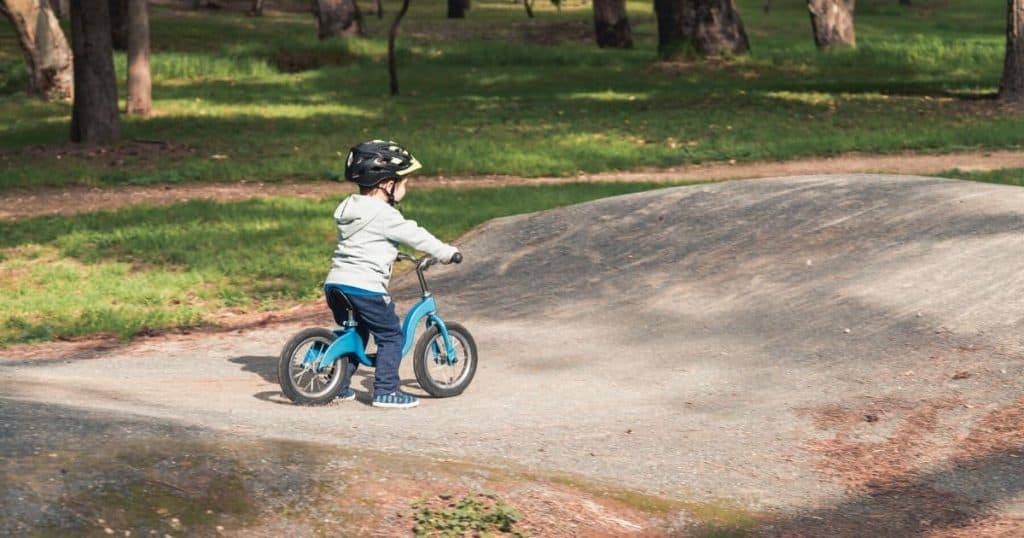 young boy about to ride up a small ramp on the best balance bike for 3 year olds