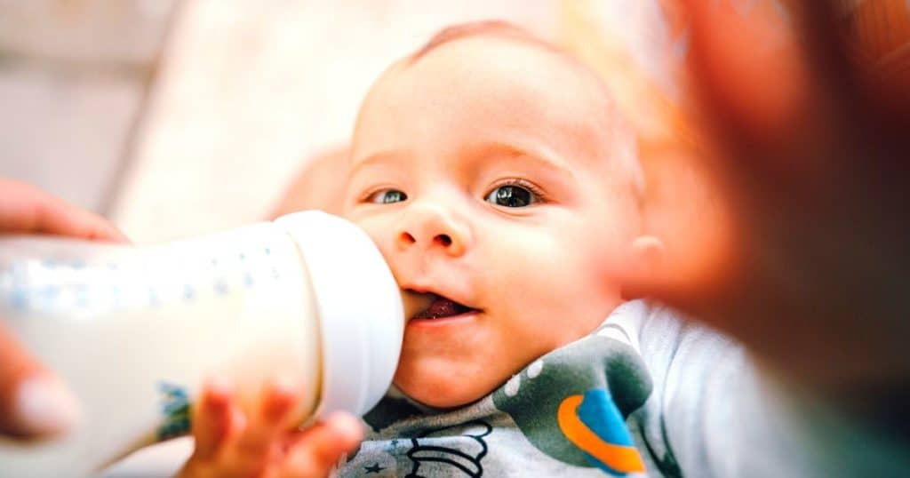 infant reaching for the camera whilst drinking from the best baby feeding bottles