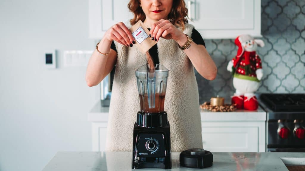 Woman using one of the best juice blenders to create a healthy juice drink