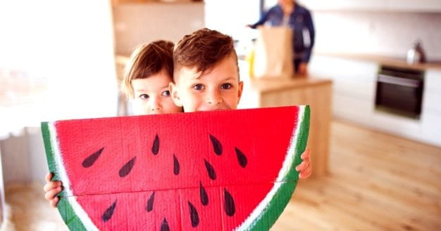Child proudly showing his watermelon crafts for kids