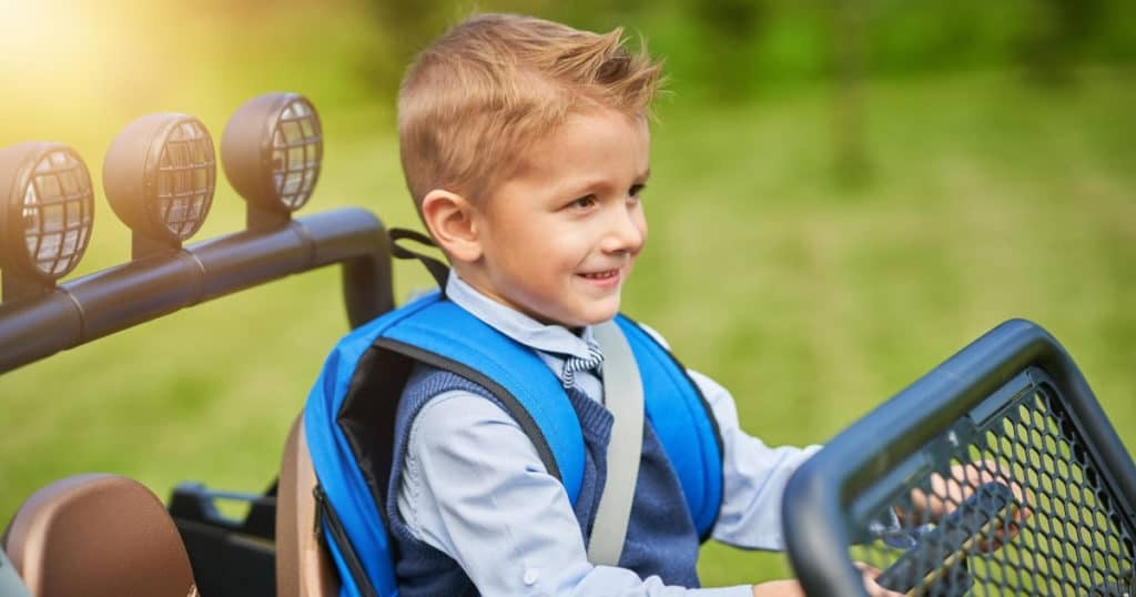 an image of a smiling boy riding the best ride on car for kids