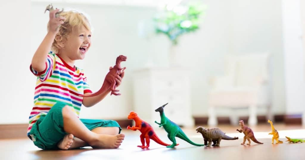 an image of a happy kid playing with the best dinosaur toys for kids
