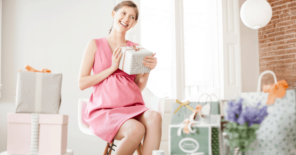 an image of a happy pregnant woman opening her gifts listed in the best baby registry