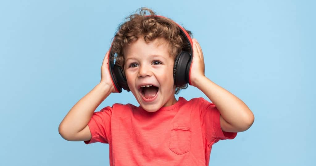 an image of happy young boy using the best headphones for kids