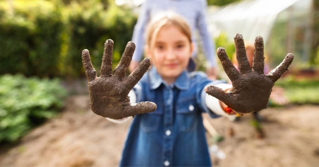 a photo of a kid's hand covered in soil